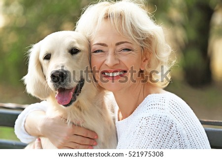 Senior woman sitting on bench with dog, closeup