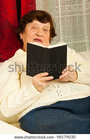 Senior woman sitting on couch and reading book in her home