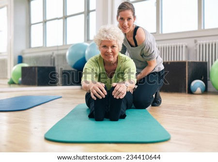 Senior woman sitting on exercise mat bending forward and touching her toes with her personal trainer assisting. Fitness training at gym with coach. - stock photo