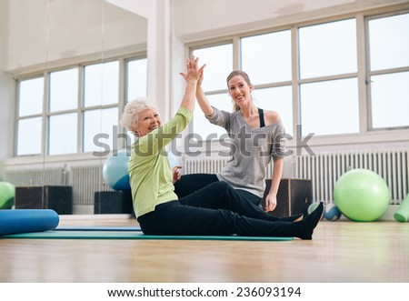 Senior woman sitting on fitness mat and her personal trainer joining hands at gym. Fitness women giving high-five at health club.