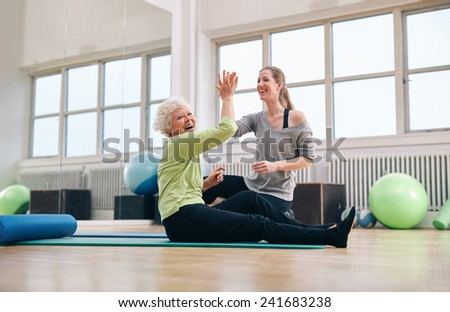 Senior woman sitting on fitness mat giving high five to her personal trainer at gym. Excited old woman rejoicing health success with her instructor at rehab. - stock photo