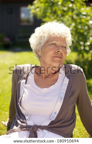 Senior woman sitting on grass with her eyes closed enjoying fresh air- Outdoors - stock photo