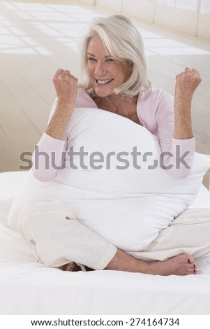 senior woman sitting on her bed clenching her fists - stock photo