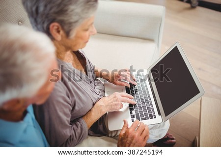 Senior woman sitting with man on sofa and using laptop in living room - stock photo