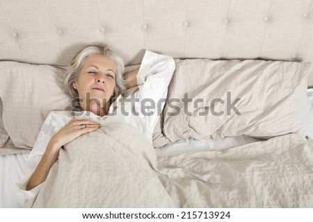 Senior woman sleeping in bed - stock photo