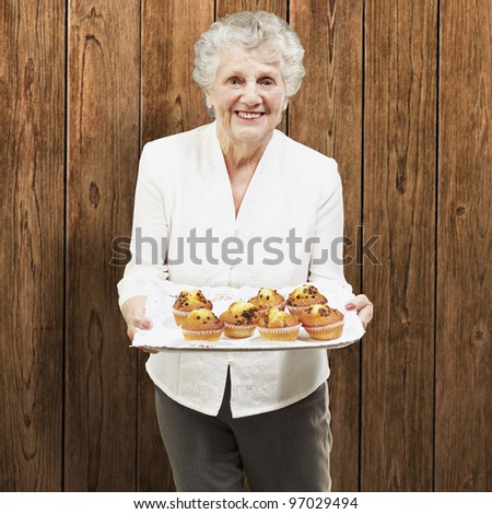 senior woman smiling and holding a tray with muffins against a wooden wall - stock photo