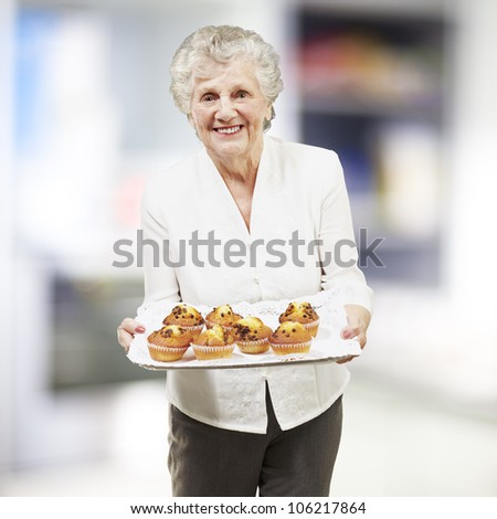 senior woman smiling and holding a tray with muffins, indoor - stock photo