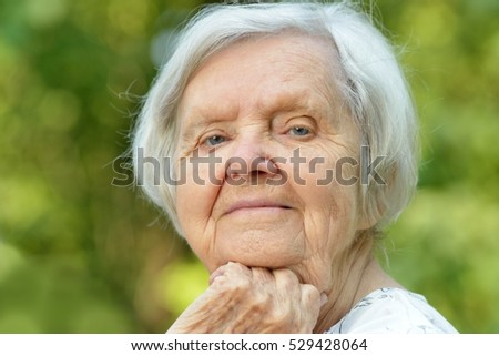 Senior woman smiling in park.