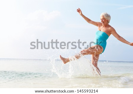 Senior Woman Splashing In Sea On Beach Holiday - stock photo