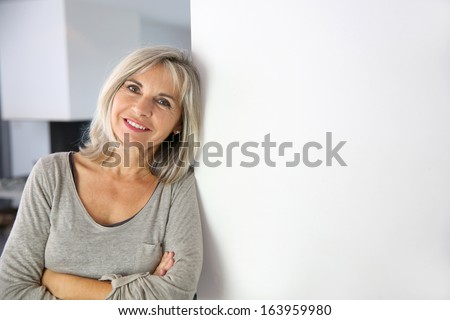 Senior woman standing against white wall - stock photo