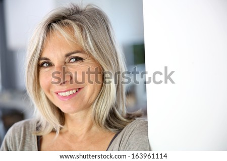 Senior woman standing against white wall - stock photo