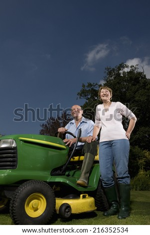 Senior woman standing next to man on riding lawn mower