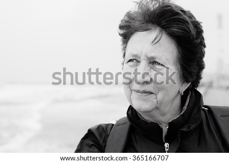 Senior woman standing on the winter beach