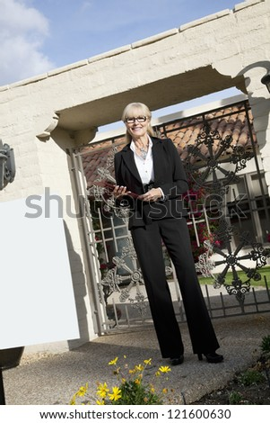 Senior woman standing with clipboard in front of entrance gate - stock photo