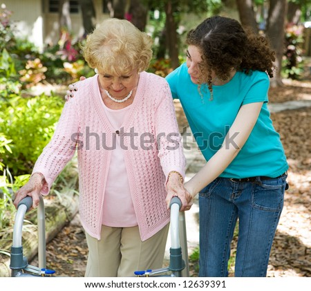 Senior woman struggles to walk with the help of a walker and her young granddaughter.