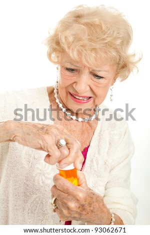 Senior woman struggling to open a childproof cap on her prescription bottle.  White background.