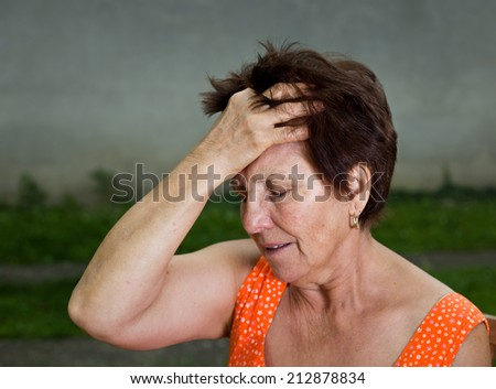 Senior woman suffers from headache, holding hand on head and have pain face - stock photo