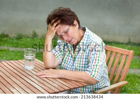 Senior woman suffers from headache, sitting at table with glass of water in front of her - stock photo