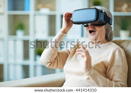 Senior woman surprising vr simulator - stock photo