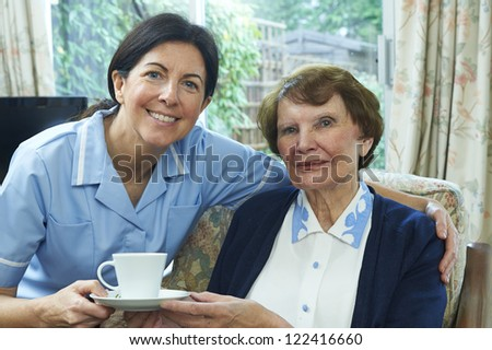 Senior Woman taking a cup of Coffee from a smiling caregiver at - stock photo