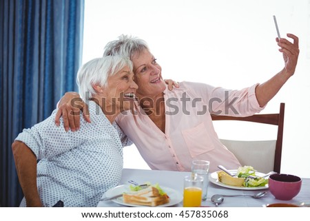 Senior woman taking a selfie during the lunch - stock photo