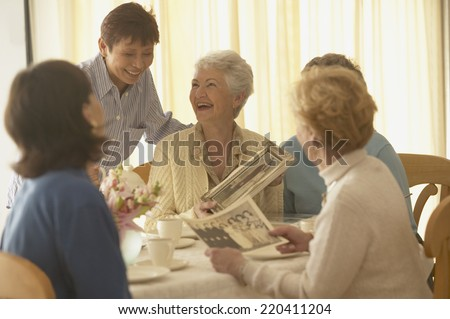 Senior woman talking and laughing with friends - stock photo