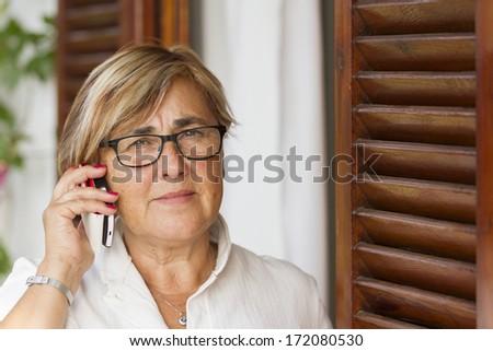 Senior woman talking on mobile phone - stock photo