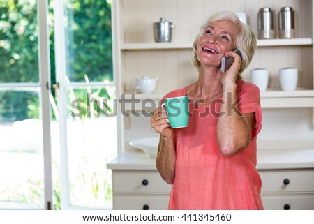 Senior woman talking on phone while having coffee in kitchen at home - stock photo