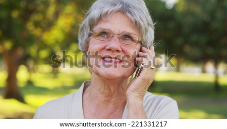 Senior woman talking on smartphone at the park