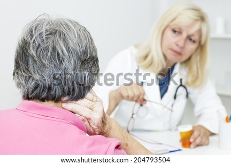 Senior woman touching her neck and talking with female doctor. - stock photo
