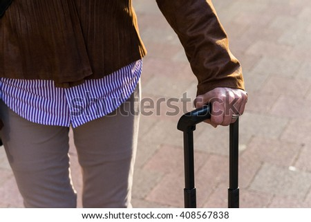 Senior woman traveling with suitcase - stock photo
