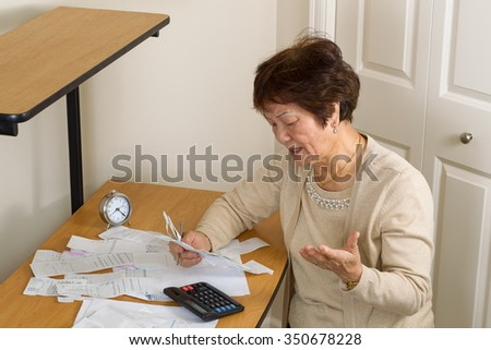 Senior woman upset at her bills. In debt concept.