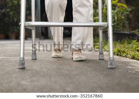 senior woman using a walker at home. - stock photo