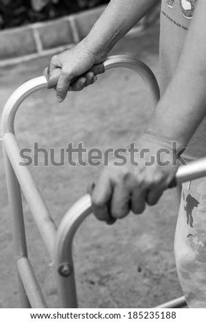 Senior woman using a walker, monochrome background, black and white background - stock photo