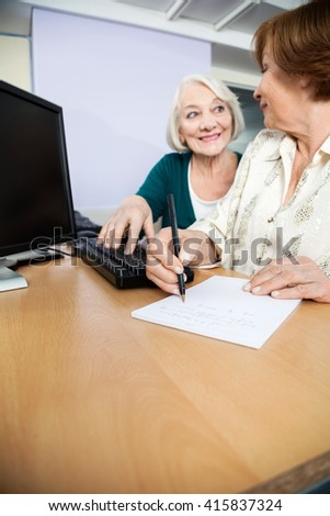 Senior Woman Using Computer While Classmate Writing Notes - stock photo