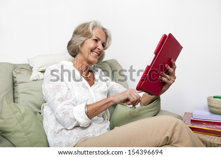 Senior woman using digital tablet on armchair at home - stock photo