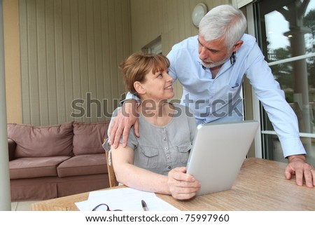 Senior woman using electronic tablet at home - stock photo