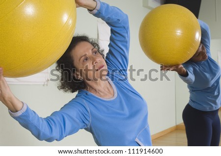 Senior woman using exercise balls in fitness class - stock photo