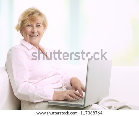 Senior woman using her laptop at home - stock photo