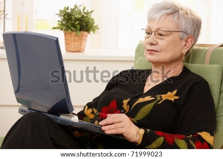 Senior woman using laptop computer at home, sitting in armchair.?