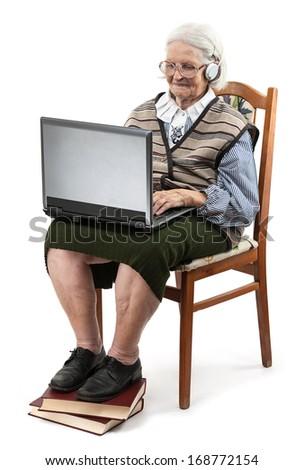 Senior woman using laptop computer isolated on white  - stock photo