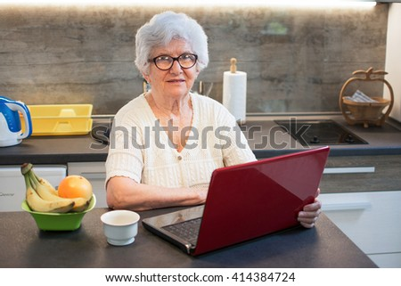 Senior woman using laptop computer while having coffee break in the kitchen.