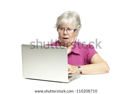Senior woman using laptop whilst looking shocked, on white background - stock photo