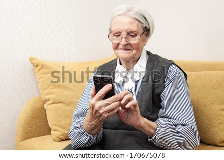 Senior woman using mobile phone while sitting on sofa  - stock photo