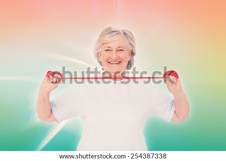 Senior woman using resistance band against abstract background - stock photo