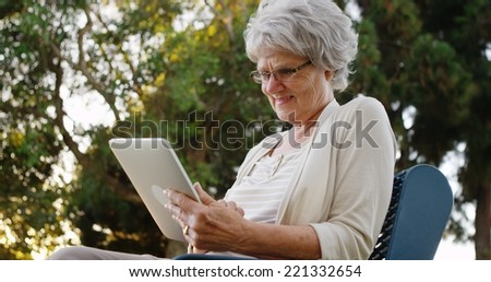 Senior woman using tablet at the park - stock photo
