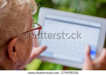 Senior woman using tablet, indoor - stock photo
