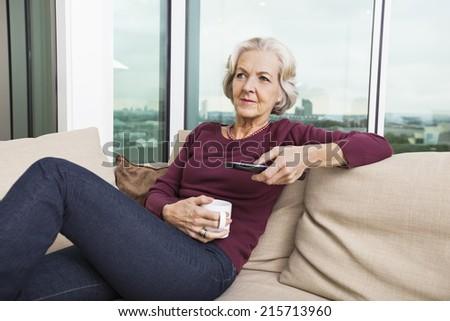 Senior woman using TV remote control on sofa at home - stock photo