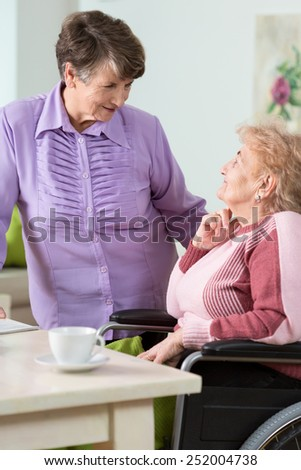 Senior woman using wheelchair and her sister - stock photo