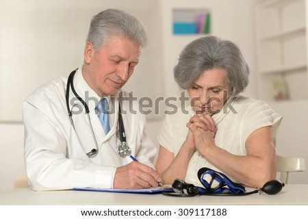 Senior woman visiting doctor at hospital - stock photo